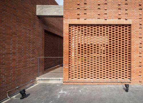 desain rumah dengan kisi batu bata yang menyamarkan area